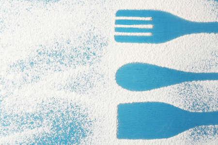 Flour sprinkled around kitchen utensils on color wooden background Stock Photo