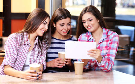 Three smiling friends with coffee looking at tablet Stock Photo