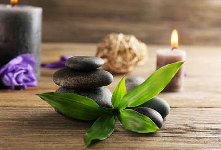 Relax set contains alight wax candles with flowers and pebbles on wooden background, focus on green leaf Stock Photo