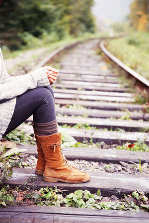 Young woman sitting on rail track Stock Photo