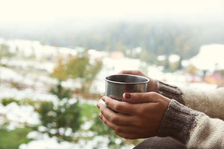 Hand holding coffee cup on mountains background