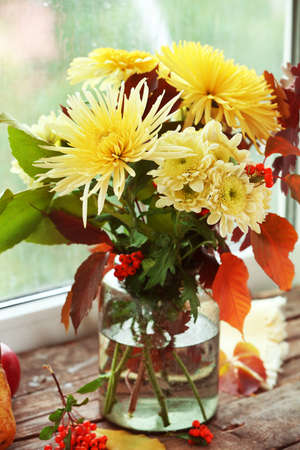 Beautiful autumn bouquet with chrysanthemums flowers, on windowsill Stock Photo