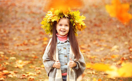 Happy young girl in yellow autumn wreath  in park