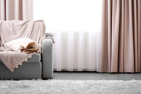 Otwarta książka na wygodnej sofie przy oknie w pokoju Zdjęcie Seryjne