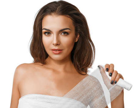 Young beautiful woman with a bandage on her chest, holding gauze, isolated on white