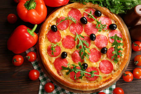Tasty pizza with salami on decorated wooden table Stock Photo