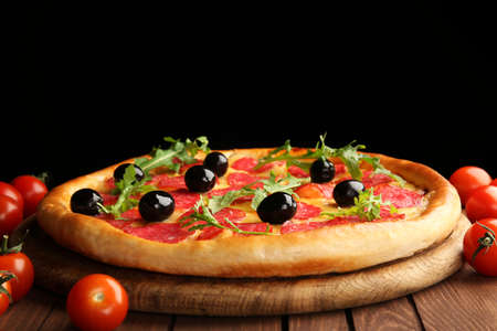 Tasty pizza with salami and olives decorated with tomatoes on wooden table against black background Stock Photo