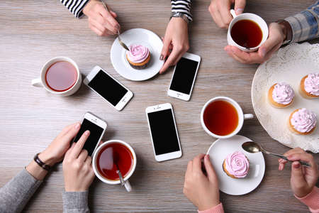 Four hands with smart phones holding  cups with tea, on wooden table background Stock Photo
