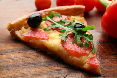 Delicious tasty piece of pizza with vegetables on wooden background, close up