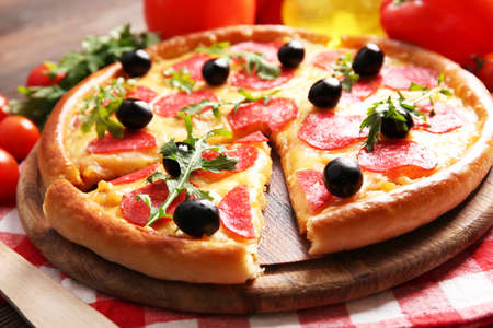 Delicious tasty pizza with salami and olives on wooden background, close up