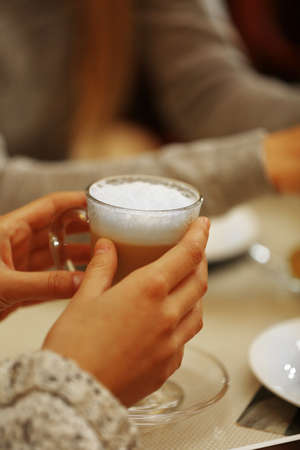 Women meeting in cafe and drinking latte Stock Photo