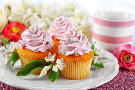 Tasty cupcakes on plate, on light background Stock Photo