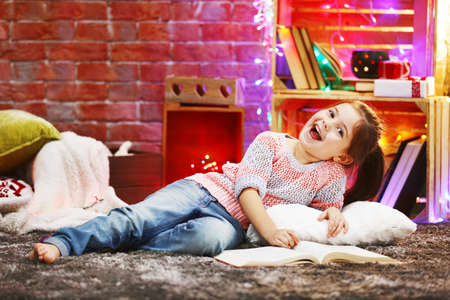 Pretty little girl with book in Christmas decorated room Stock Photo