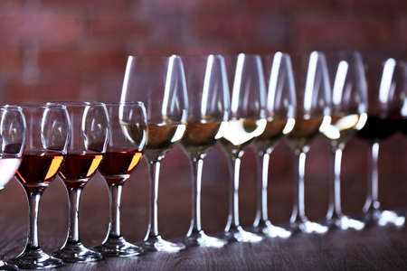 Wineglasses with white, red and pink wine on wooden table on wall brick background Stock Photo