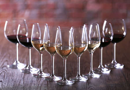 Wineglasses with white, red and pink wine on wooden table close-up Stock Photo