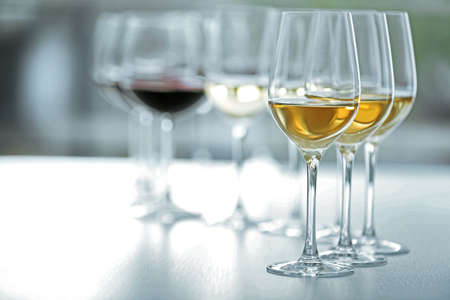Wineglasses with white and red wine on wooden table on bright background Stock Photo