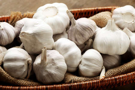 Garlic in wicker bowl on wooden background, close up Stock Photo