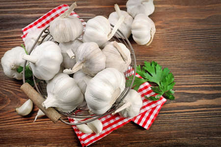 Fresh garlic in the basket decorated with parsley and red checkered cotton napkin on wooden background