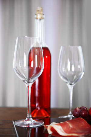 Pink wine bottle, two wineglasses, grape, slice of bacon on a table, still life