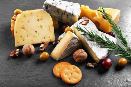 Composition of fresh cheese, fruits and vegetables on black background, close up