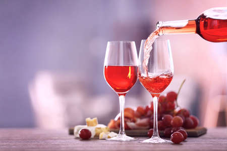 Pouring pink wine from bottle into the wineglass on blurred background Stock Photo