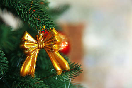 Christmas toy on a fir tree over blurred background, close-up