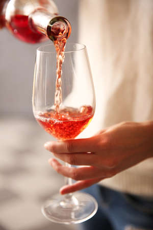 Young woman pouring pink wine into glass on blurred background Foto de archivo