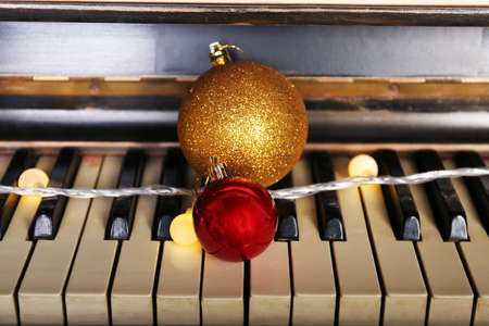 Piano keys decorated with decorative lights and balls, close up