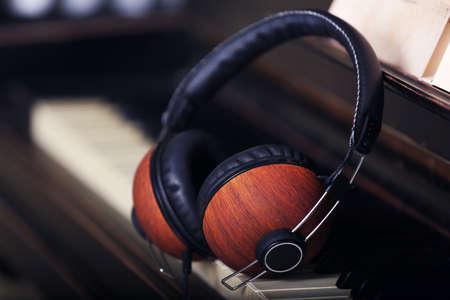Brown headphones on piano keyboard, close up 写真素材