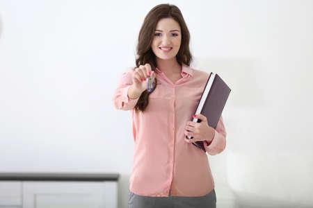 Friendly female estate-agent on light background
