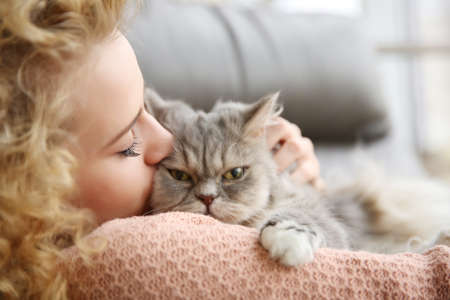 Young woman and cat on sofa in the room