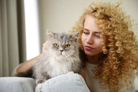 Young woman and cat in the room Stock Photo