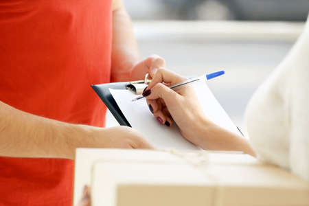 Woman signing receipt of delivery package, close up Stock Photo