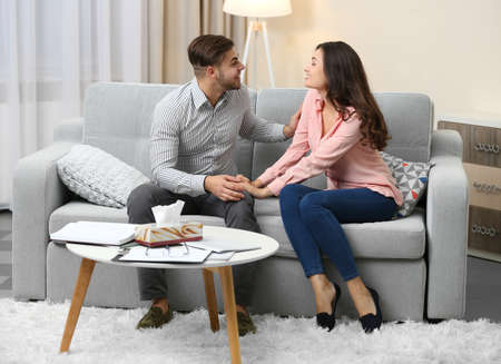 Happy couple on sofa, on home interior background Banque d'images