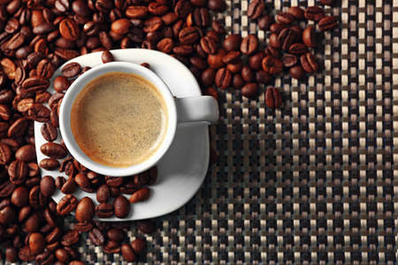 Cup of coffee and coffee grains on dark background Stock Photo