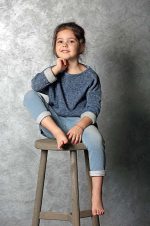 Portrait of little fashion kid girl on gray wall background Stock Photo