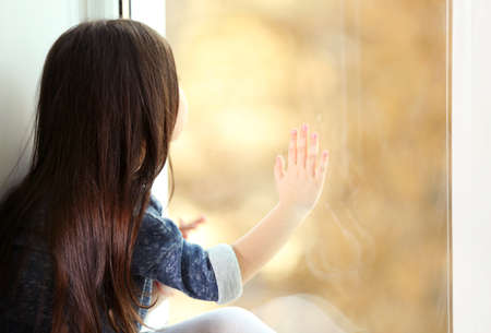 Little girl waiting for someone and looking out the window Imagens