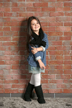 Portrait of little fashion kid girl on bricks wall background Banque d'images