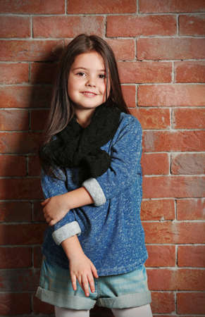 Portrait of little fashion kid girl on bricks wall background Standard-Bild