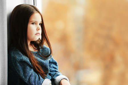 Little girl waiting for someone and looking out the window Stock Photo