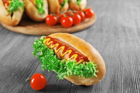 Tasty hot-dog with tomatoes on wooden table