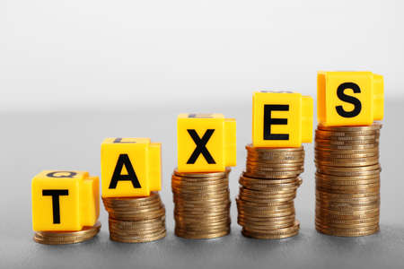 Alphabet TAXES and golden coins on table