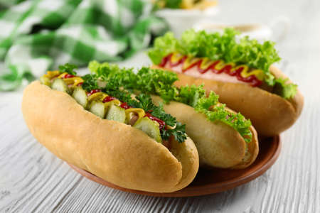 Delicious hot-dogs on white wooden table, close up