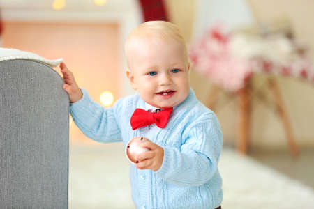 Funny baby on soft carpet near sofa and Christmas tree on background