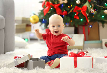 Funny baby with gift boxes and Christmas tree on background