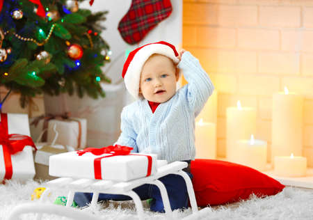 Funny baby  sitting near sledge and Christmas tree and fireplace on background Stock Photo