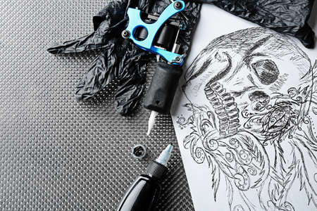 Tattoo machine, sketch and tattoo supplies, close up