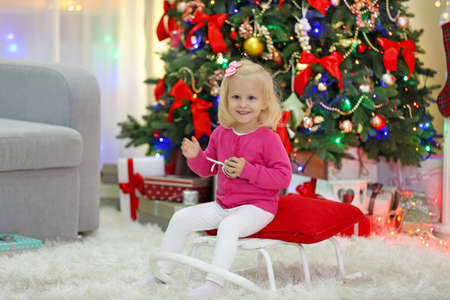 Funny girl  in living room and Christmas tree on background Stock Photo