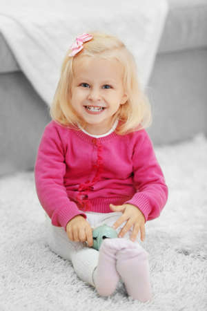 Little girl with Christmas toy, sitting on fluffy carpet