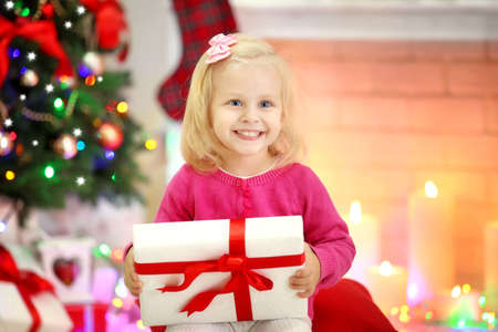 Funny girl with gift boxes and Christmas tree on background